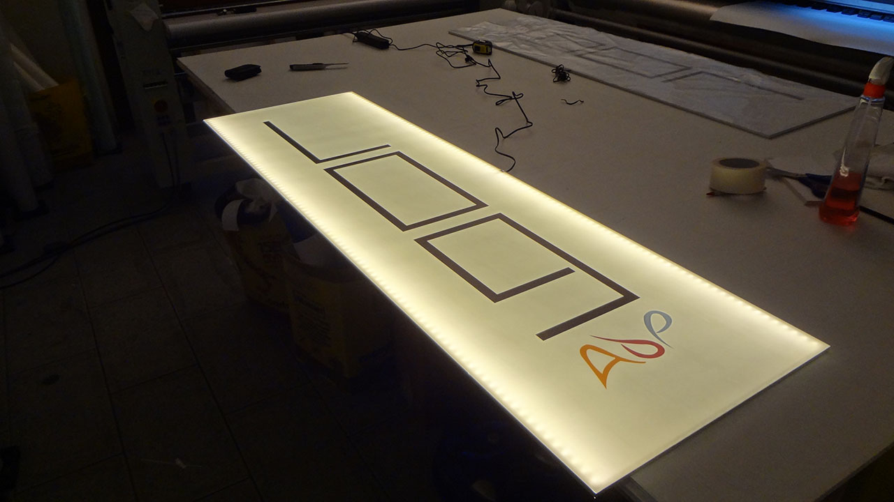 Insegna luminosa a LED bifacciale con staffa per montaggio.
